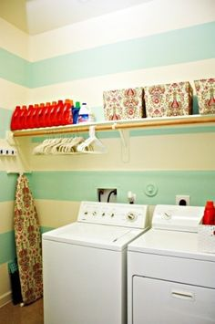 """First, I like this simple space. It's an open shelf with a rod for hanging your """"just dried"""" laundry. There are bins on top to hide any unsightly things - but they can be labeled and organize light bulbs, etc. You could even add a second shelf to put stuff higher up that you don't use as often. I love the stripes in here because it makes the laundry room seem bigger than it is."""