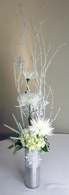Imagine black Dahlia's in the place of the white mums--deep blue hydrangea instead of white--no snowflake-duh and black branches. Put it in the mercury glass (mirror silver) vase. Pretty and very simple and adds a nice element of height.