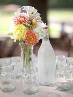 Eclectic twist on mason jar centerpiece--jars start out as decor, end up as drinking glasses (anyone know what kind of bottle that is with the topper?).