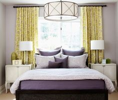 Bed in front of window--different color drapes not all the way to wall.