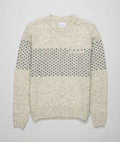 A crewneck style featuring an engineered pattern across the chest in natural, undyed yarn.