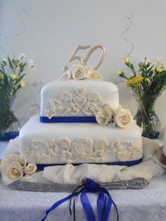 50th Wedding Anniversary Cake - A white fondant cake with gold gumpaste appliques and flowers.  Blue satin ribbon to match party theme.  Appliques were done with the new Wilton Baroque silicone mold.  First time using that.  It works awesome!!!  Was a really fun cake to do!