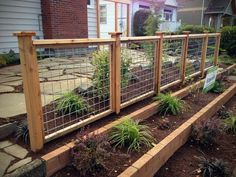 DIY retaining wall planter in front of cedar hig panel fence for added curb appeal