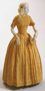 Dress    Made in United States  c. 1840    Artist/maker unknown, American    Gold china silk , crepe weave, satin stitch embroidery in matching silk thread  Center Back Length: 53 1/4 inches (135.3 cm)