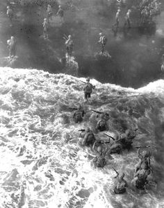 Description of  December 26, 1943: U.S. Marines are seen from above as they wade through rough water to take the beach at Cape Gloucester on New Britain, Papua New Guinea. (AP Photo)