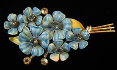 This is a beautiful, vintage rhinestone and enamel brooch.  It is silver toned with blue enamel flowers and light green leaves. They are highlighted by blue and aurora rhinestones.