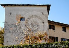 Photo made at the castle and the village of Strassoldo Friuli (Italy). In the image, obtained from the lawn in front of the south side of the castle, you can see the entire facade of the castle, which is located opposite the church of St. Nicholas in particular the upper part which lies to the east and on which there is a single small window.