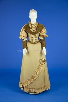 1893 Tan Silk Wedding DresTan silk gown having a double-breasted bodice trimmed with black and tan stripe wide lapels, lower part of leg-of-mutton sleeves and bottom of bodice. Wide tan satin ribbons and large paisley buttons also embellish bodice. The five-gore A-line skirt is cartridge pleated center back and trimmed with a gathered self-fabric band at hem which sweeps asymmetrically up to another satin bow on left front of skirt. 1893