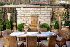 Patio with Iron and stone table with light colored wicker chairs. Terra-cotta pots and boxwoods.