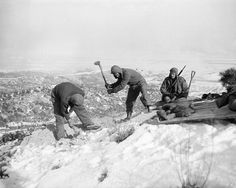 GI's use entrenching tools as they dig in Korean hilltop North of Seoul, South Korean capital on Jan. 8, 1951. A burning village in background sends up smoke pillar. From left are: Pfc. Walter Madjarac, Cleveland, Ohio; Pvt. Norman Wolak, Chicago, and Cpl. Chet Collett, of Troy, Ohio. (AP Photo/ENH)