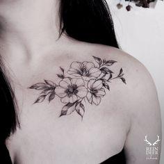 Medium size blackwork style collarbone tattoo of little flowers