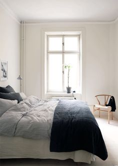 gray bedding with black blanket at the foot of the bed