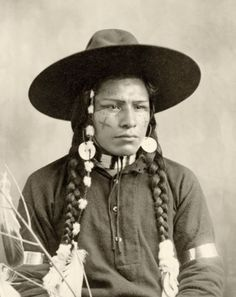 A young man in a mixture of traditional and store-bought attire sits solemnly for a portrait, ca 1903. At the turn of the last century, portraits of Native Americans were all the rage, and many photographers jumped in to create views for sale. Often they dressed their subjects in props they had accumulated from a mixture of tribes. This photo was taken by Dio D. Wilder in The Dalles, Oregon.