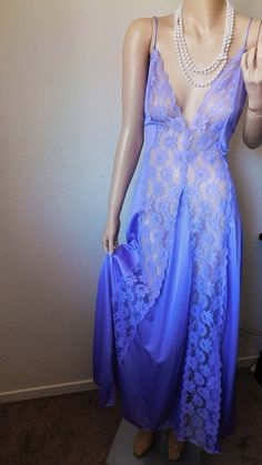 This beautiful long nightgown is as elegant as they come. This piece is in a beautiful lavender purple color. This piece has two sheer lace strips from the top of the cups to the hem of the nightgown. There are spaghetti straps at the top and a deep v-neckline. The back has a low cut to show of your sexy skin. This piece is simple and very stunning.  This item is in excellent vintage condition.  Size Large Bust - 40-46 Waist - 34-42 Hips - 52+ This item is made of 100% nylon and does…