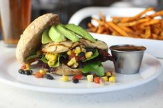 Chicken, black bean and corn salsa, organic mixed greens, avocado, on a multigrain bun with bbq sauce on the side. Oh, and some sweet potato fries in the background :)