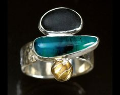 The ring features a unique-cut sand blasted black jade cabochon and one 3.95 carat peruvian opal cabochon.  Amazing Artist from Illinois
