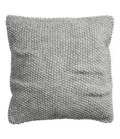 Een kussenhoes met een ingebreid gerstekorreldessin aan de voorkant en geweven katoen aan de achterkant. Blinde ritssluiting.