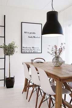 Scandinavian inspired apartment dining room with oversized industrial pendant light. Black and white space is softened with the addition of the timber table
