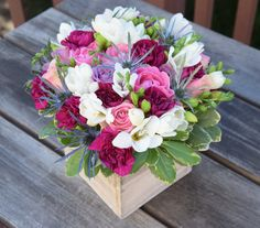 Floral gift in a box: roses, freesia, mini carnations and thistle.