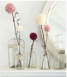 Twigs and yarn poms in apothecary bottles.