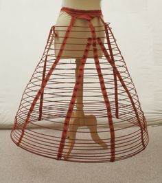 Cage crinoline  National Trust Inventory Number 1350050  Category: Costume  Date 1860 - 1870  Materials Cotton, Steel, Wool  Cage crinoline - Made from red webbing and cotton tabby and 26 sprung steel hoops held in position with 9 strips of webbing. It is marked Thomson Prize Model Skirt.....Royal Letters Patent on waistband. (female) (foundation garments)   Collection: Snowshill Wade Costume Collection, Gloucestershire (UK)