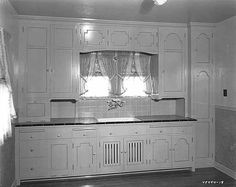 1930s kitchen, inspiration for cottage style kitchens. Minimal decoration, solid light cabinet color, upper cabinets, faux feet.