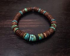 Stacking Heishi mens bracelet, natural Heishi Turquoise 8-9 mm and coco wood rondelles strung on strong elastic . Handmade, rustic, earthy, you just have to roll it on your wrist. Can be worn alone or stacked.- Overview: Guaranteed without nickel, lead free, cadium free Heishi