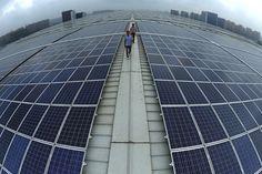 IlPost - Hangzhou, Cina - Due uomini camminano sul tetto della stazione dei treni di Hangzhou East, completamente ricoperto di pannelli solari  (AP Photo)