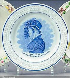 A blue and white plate, ca. 1820: pearlware transfer-printed in blue with a bust portrait of Queen Caroline wearing a plumed hat above title, beneath a moulded border