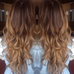 Warm toned balayage ombre color melt long hair with curls