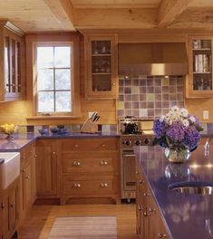 Kitchen sports lavender tile and blue-violet counters. Bold kitchen done up in summer florals that read from cobalt to lavender – a nod to the range of colors found in hydrangeas.