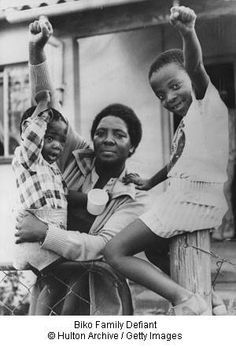 """Biko Family Defiant  [Click on this image to find a short video and analysis of the conditions of apartheid in South Africa and why that system of oppression is comparable to Jim Crow segregation in the U.S.]  Ntsiki Biko, widow of South African political detainee Steve Biko, defiantly gives the Black Power salute with her children Samora (left) aged two, and Nkosinathi aged six, in front of their home at King William's Town, South Africa...""""  Photo credit: Hulton Archive / Getty Images"""