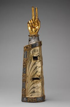 Reliquary Arm, ca. 1230  South Netherlandish  Silver over oak; hand: bronze-gilt; appliqué plaques: silver-gilt, niello and cabochon stones ☩