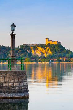 Italy, Piedmont, Lake Maggiore, La Rocca fortress viewed from Arona at sunset