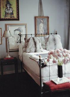 classic iron bed. faux fur pillows = good idea