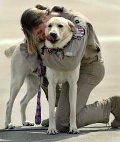 "Mary Melfi hugs her dog ""Glory"" after being reunited with him for the first time since being deployed as part of the U.S. war with Iraq. (2006)"