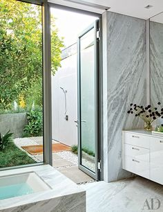 MASTER BATH The marble-clad master bath, which includes a Poliform vanity with a Caesarstone top, adjoins an outdoor shower with Dornbracht fittings.