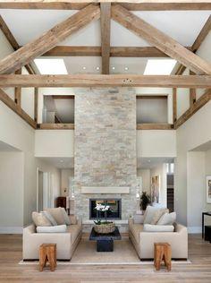 salon avec un haut plafond avec murs en pierres