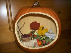 Miniature Fall Display / Diorama inside of a Funkin Pumpkin! I used hot glue gun, reindeer moss, model railroad mini trees, other dollhouse miniatures, hay bale, flower pot, scarecrow, some mini silk fall leaves.  I used the little pumpkin saw that comes in kit to carve real pumpkins. Easy to saw open.