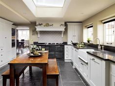 harvest table with benches, colonial cabinetry, AGA, oversized slate floor tiles, apron sink with high-arch faucet, deep counters, no cabinet above work surfaces, sky light above table. Kitchen extensions | Period Living
