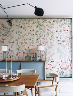 Floral wall covering, blue sideboard, mid century dining table. Eclectic and inviting space.