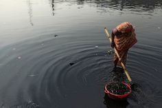 WASTE DUMP: A woman washed plastic particles in a river in Dhaka, Bangladesh, Friday. A large swath of the Buriganga River has turned pitch-black with toxic waste, oil and chemicals flowing into it from industrial units. (Abir Abdullah/European Pressphoto Agency)