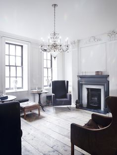 """This beautiful old-world space has been given the """"natural glam"""" treatment, with stripped-down plank flooring and white-washed plasterwork, made more contemporary by the mix of solid-colour furniture from different decades. Here, you can see how a traditional chandelier, like Schonbek's Bagatelle Crystal Chandelier, stands out amid the more modern pieces, working with the rest of the decor to create the feel of more relaxed sophistication."""