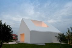 """Windowless House in Leiria Portugal by Aires Mateus & Associados. """"The private areas are at street level under the plot, around a central courtyard with rooms opening to private patios in a intimate environment. The living rooms are around a void, that collects light from above and gazes the castle at the city center."""""""