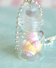 This necklace features a miniature jar of handmade cupcakes with pink frosting sculpted from polymer clay. The glass jar measures about 2.5 cm tall and is securely attached to a silver tone ball chain