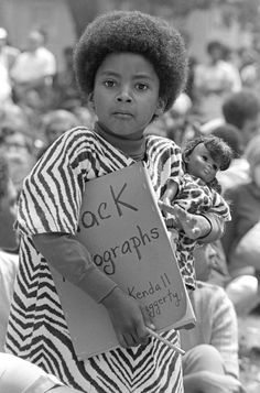 """Kendall Haggerty with a """"Black Autographs"""" folder and Black doll at a """"Free Huey"""" rally, DeFremery Park, 1968.  Photo credit: Bob Fitch — in Oakland, California."""