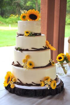 Round Wedding Cakes - Modern, rustic wedding cake for an outdoor wedding. 4 offset tiers with fondant twig border and handmade sugar flowers consisting of sunflowers, ranunculus, billy balls, berries, and pulled sugar blossoms.