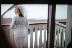 Matt Shumate Photography at Schweitzer Mountain Resort winter wedding bride looking outside on balcony for her winter wedding wondering about the weather in a white snow suit and veil