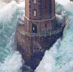 Yes, the picture is real. Believe it or not, the man in the lighthouse was not killed.  He was awaiting rescue via helicopter.  That was the only reason he opened the door.