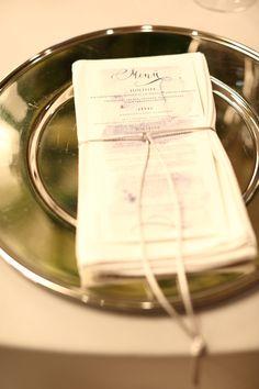 Ezüst alaptányér - bele: menükártya kerül.  Alatta / körülötte / felette: damaszt szalvéta.